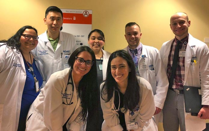 Dr. Rosado and her team of interns, seniors and pharmacists  take time to smile after morning floor rounds.